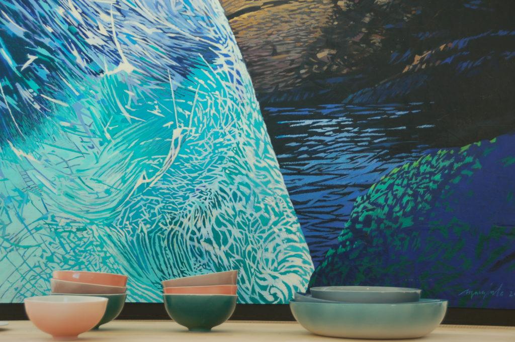 """Aurore : bols en porcelaine couleurs du ciel au lever du soleil sur l'océan Breton. 14 cm, vert, rose, violet, orange. Accompagnés d'une série de plats de cuisson """"Océan"""" dans trois tons marines. 30  cm, 24 x 20 cm et 18 cm. Le tableau dans le fond, de mon ami Patrick Marziale represente la mer entre les rochers. style contemporain, coloré en tons de turquoise, bleu et brun."""