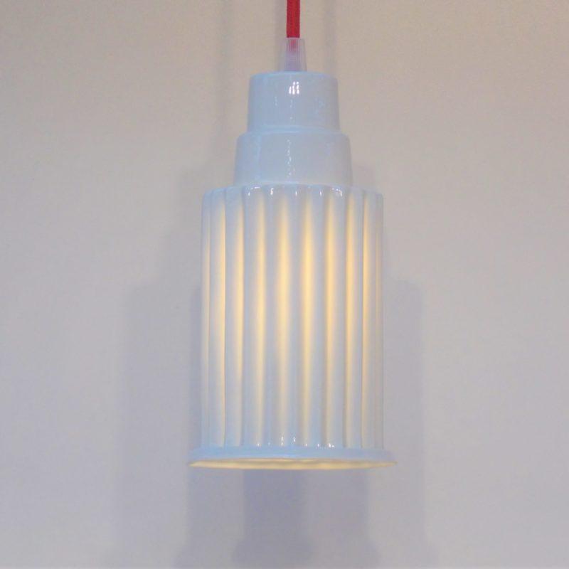 Arabica est une lampe suspendue. La lumière filtre avec douceur à travers la porcelaine. livré avec ampoule E14 LED et cordon rouge coton.